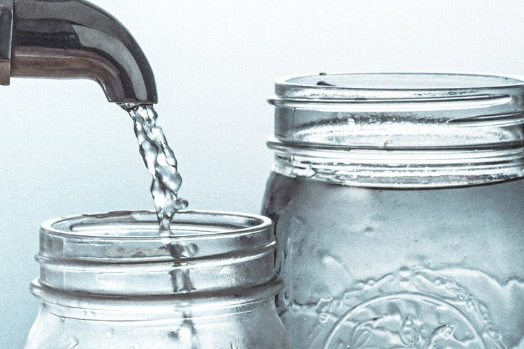 Pouring water into a Mason jar from a faucet.